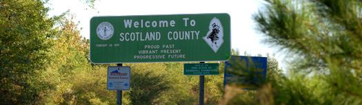 The Welcome to Scotland County sign with trees around it